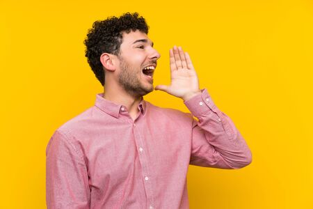 Man with curly hair over isolated yellow wall shouting with mouth wide open
