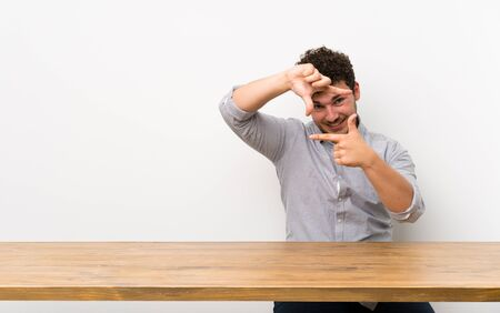 Young man with a table focusing face. Framing symbol