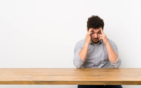 Young man with a table with headache