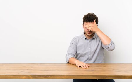 Young man with a table covering eyes by hands. Do not want to see something Stock Photo