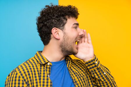 Man with curly hair over colorful wall shouting with mouth wide open