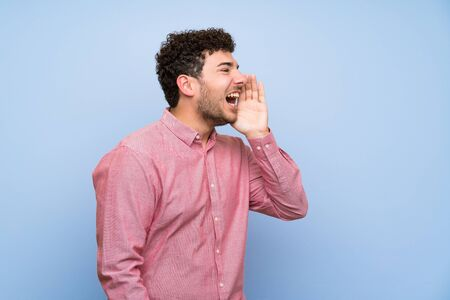 Man with curly hair over isolated blue wall shouting with mouth wide open to the lateral Imagens