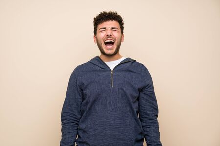 Man with curly hair over isolated wall shouting to the front with mouth wide open Imagens