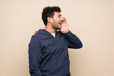Man with curly hair over isolated wall shouting with mouth wide open to the lateral Imagens