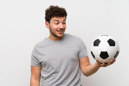 Man with curly hair over isolated wall holding a soccer ball Stockfoto - 128814598