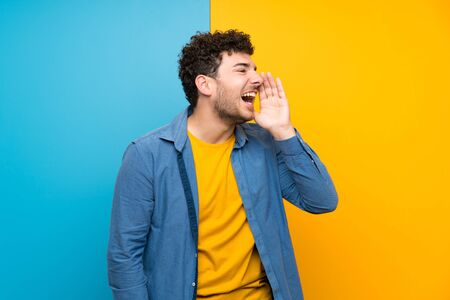 Man with curly hair over colorful wall shouting with mouth wide open to the lateral