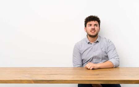 Young man with a table with confuse face expression