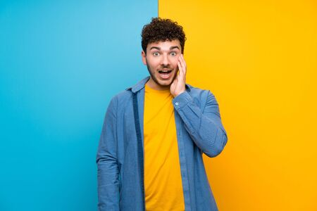 Man with curly hair over colorful wall with surprise and shocked facial expression Stok Fotoğraf