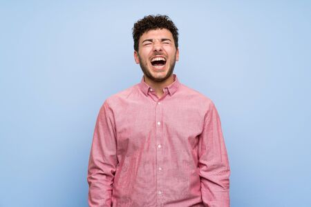 Man with curly hair over isolated blue wall shouting to the front with mouth wide open Imagens