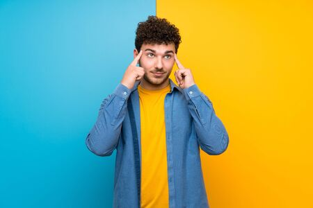 Man with curly hair over colorful wall having doubts and thinking