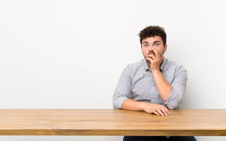 Young man with a table surprised and shocked while looking right