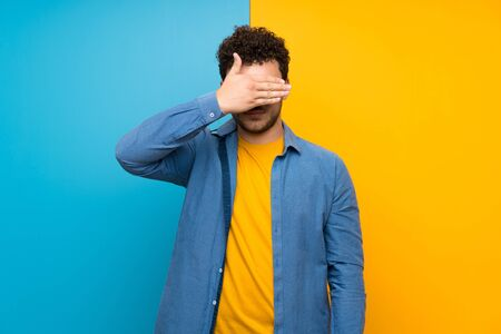 Man with curly hair over colorful wall covering eyes by hands. Do not want to see something Stock Photo