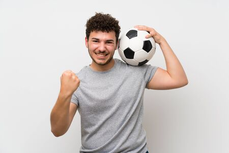 Man with curly hair over isolated wall holding a soccer ball