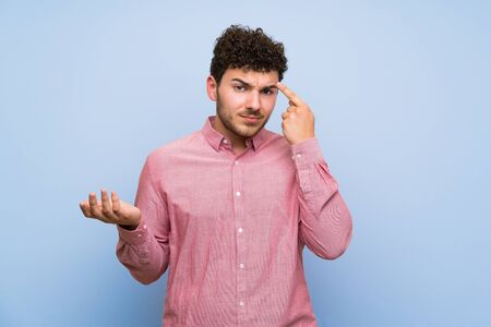 Man with curly hair over isolated blue wall making the gesture of madness putting finger on the head