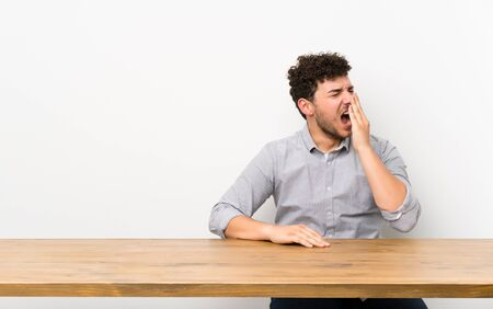 Young man with a table yawning and covering wide open mouth with hand Imagens