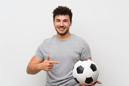 Man with curly hair over isolated wall holding a soccer ball Stockfoto - 128816659