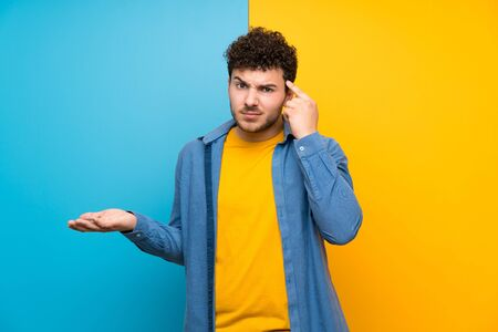 Man with curly hair over colorful wall making the gesture of madness putting finger on the head