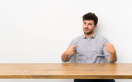 Young man with a table proud and self-satisfied