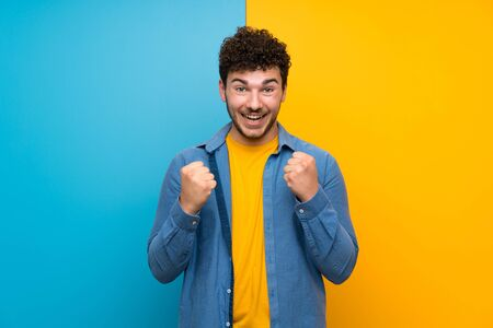 Man with curly hair over colorful wall celebrating a victory in winner position