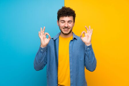 Man with curly hair over colorful wall in zen pose Imagens