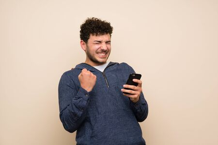 Man with curly hair over isolated wall with phone in victory position