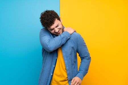 Man with curly hair over colorful wall suffering from pain in shoulder for having made an effort
