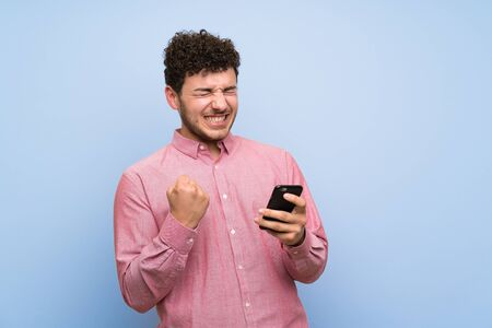 Man with curly hair over isolated blue wall with phone in victory position Imagens