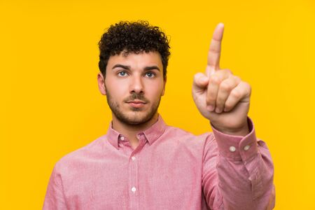 Man with curly hair over isolated yellow wall touching on transparent screen Banco de Imagens