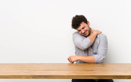 Young man with a table suffering from pain in shoulder for having made an effort