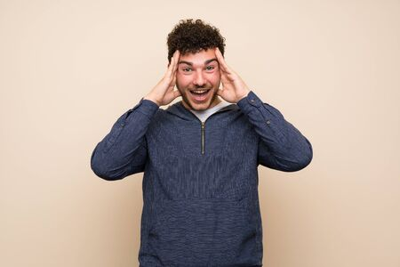 Man with curly hair over isolated wall with surprise expression Stok Fotoğraf