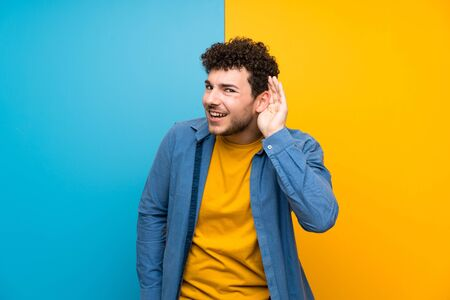Man with curly hair over colorful wall listening to something by putting hand on the ear Foto de archivo