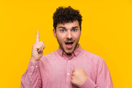 Man with curly hair over isolated yellow wall with surprise facial expression Imagens