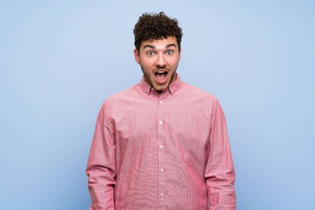 Man with curly hair over isolated blue wall with surprise facial expression Stok Fotoğraf