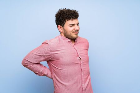 Man with curly hair over isolated blue wall suffering from backache for having made an effort