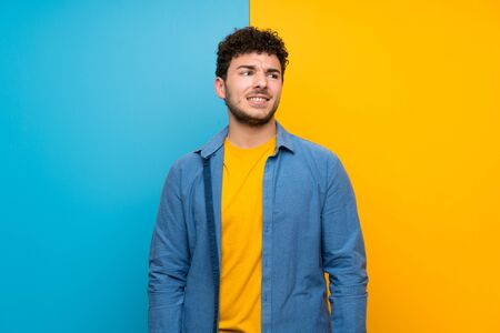 Man with curly hair over colorful wall with confuse face expression