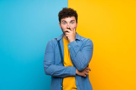 Man with curly hair over colorful wall surprised and shocked while looking right