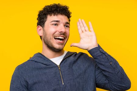 Young man over isolated yellow wall shouting with mouth wide open Imagens