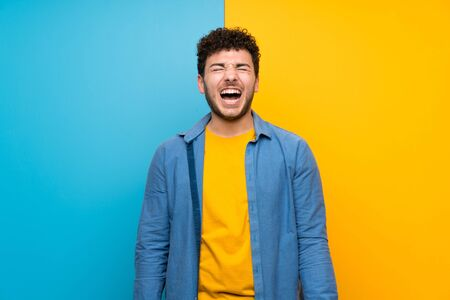 Man with curly hair over colorful wall shouting to the front with mouth wide open Imagens
