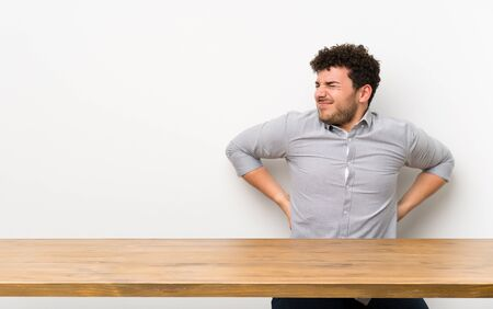 Young man with a table suffering from backache for having made an effort