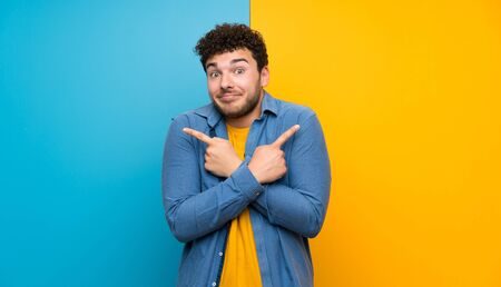 Hombre con cabello rizado sobre pared colorida apuntando a los laterales teniendo dudas Foto de archivo