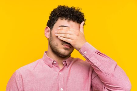 Man with curly hair over isolated yellow wall covering eyes by hands