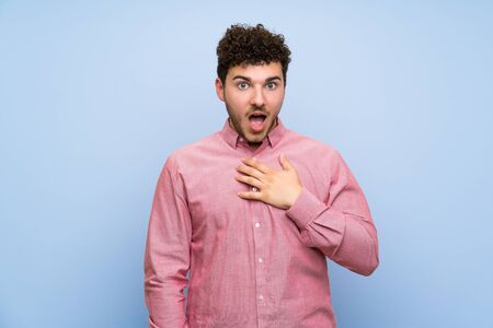 Man with curly hair over isolated blue wall surprised and shocked while looking right