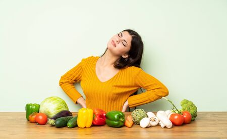 Teenager girl with many vegetables suffering from backache for having made an effort