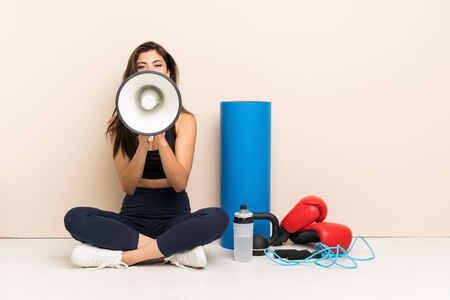Teenager sport girl sitting on the floor shouting through a megaphone