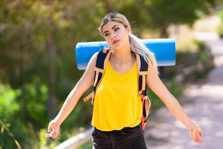 Teenager girl hiking at outdoors having doubts while raising hands Foto de archivo