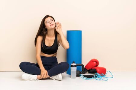 Teenager sport girl sitting on the floor listening to something by putting hand on the ear