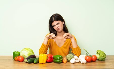 Teenager girl with many vegetables showing thumb down