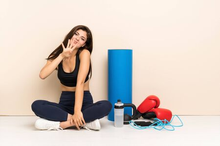 Teenager sport girl sitting on the floor happy and counting four with fingers Banque d'images - 129065759