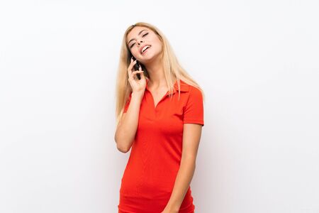 Teenager girl over isolated white background keeping a conversation with the mobile phone