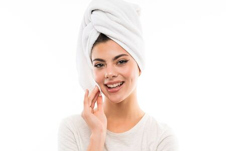 Teenager girl over isolated white backgroundremoving makeup from her face with cotton pad